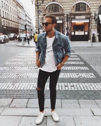 Wie kombinieren: blaue Jeansjacke, weißes und schwarzes bedrucktes T-Shirt mit einem Rundhalsausschnitt, schwarze enge Jeans mit Destroyed-Effekten, weiße Leder niedrige Sneakers