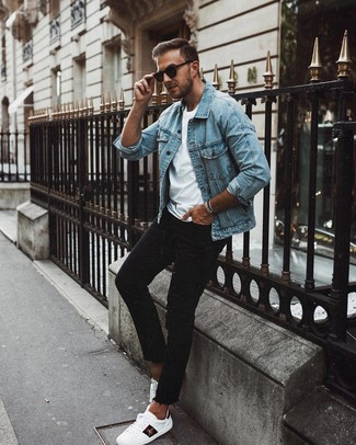 Wie kombinieren: hellblaue Jeansjacke, weißes T-Shirt mit einem Rundhalsausschnitt, schwarze enge Jeans, weiße bedruckte Leder niedrige Sneakers