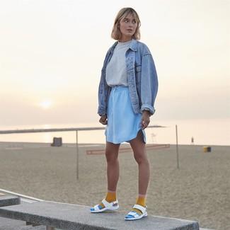 Damen Outfits & Modetrends 2020: Eine hellblaue Jeansjacke und ein hellblauer Minirock sind sehr gut geeignet, um einen lässigen Look zu erzeugen. Fühlen Sie sich mutig? Entscheiden Sie sich für weißen flache Sandalen aus Leder.