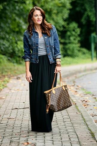 Wie kombinieren: dunkelblaue Jeansjacke, graues T-Shirt mit einem V-Ausschnitt, schwarzer Falten Maxirock, dunkelbraune bedruckte Shopper Tasche aus Leder