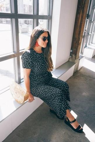 Rote Ohrringe kombinieren: trends 2020: Wenn Sie ein entspanntes Trend-Outfit zaubern möchten, macht die Paarung aus einem schwarzen und weißen gepunkteten Jumpsuit und roten Ohrringen Sinn. Schwarze flache Sandalen aus Leder sind eine ideale Wahl, um dieses Outfit zu vervollständigen.