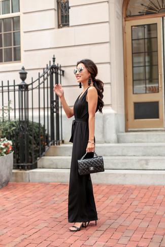 Wie kombinieren: schwarzer Jumpsuit, schwarze Leder Sandaletten, schwarze gesteppte Satchel-Tasche aus Leder, silberne Sonnenbrille