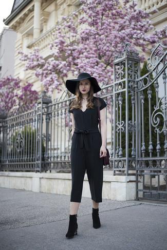 Wie kombinieren: schwarzer Jumpsuit, schwarze verzierte Wildleder Stiefeletten, lila Shopper Tasche aus Wildleder, schwarzer Hut