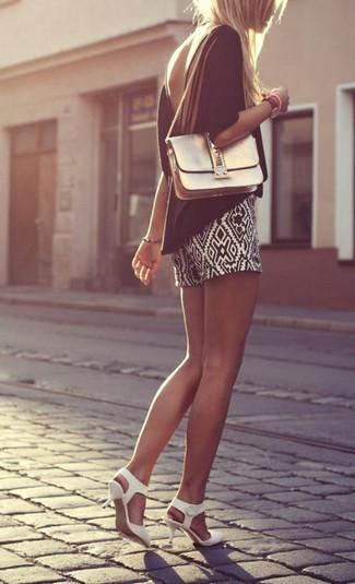 Wie kombinieren: schwarze Kurzarmbluse, schwarze und weiße Shorts mit geometrischen Mustern, weiße Leder Pumps, goldene Leder Umhängetasche