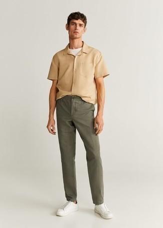 Casual Outfits Herren 2020: Kombinieren Sie ein beige Kurzarmhemd mit einer olivgrünen Chinohose, um mühelos alles zu meistern, was auch immer der Tag bringen mag. Vervollständigen Sie Ihr Look mit weißen Segeltuch niedrigen Sneakers.