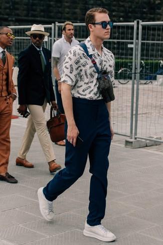 Wie kombinieren: weißes und dunkelblaues bedrucktes Kurzarmhemd, dunkelblaue Chinohose, weiße Leder niedrige Sneakers, schwarze Leder Bauchtasche