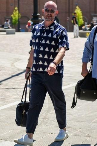 Weiße Leder niedrige Sneakers kombinieren: Casual-Outfits: trends 2020: Tragen Sie ein dunkelblaues und weißes bedrucktes Kurzarmhemd und eine dunkelblaue Chinohose für ein bequemes Outfit, das außerdem gut zusammen passt. Dieses Outfit passt hervorragend zusammen mit weißen Leder niedrigen Sneakers.