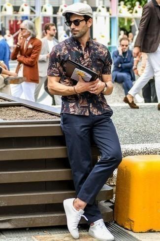 Weiße Leder niedrige Sneakers kombinieren: Casual-Outfits: trends 2020: Vereinigen Sie ein dunkelblaues bedrucktes Kurzarmhemd mit einer dunkelblauen Chinohose für ein sonntägliches Mittagessen mit Freunden. Weiße Leder niedrige Sneakers fügen sich nahtlos in einer Vielzahl von Outfits ein.