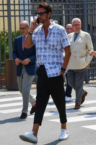 Weiße Leder niedrige Sneakers kombinieren: Casual-Outfits: trends 2020: Kombinieren Sie ein weißes und schwarzes bedrucktes Kurzarmhemd mit einer schwarzen Chinohose für ein bequemes Outfit, das außerdem gut zusammen passt. Komplettieren Sie Ihr Outfit mit weißen Leder niedrigen Sneakers.