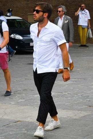 Weiße Leder niedrige Sneakers kombinieren: Casual-Outfits: trends 2020: Tragen Sie ein weißes Kurzarmhemd und eine schwarze vertikal gestreifte Chinohose, um mühelos alles zu meistern, was auch immer der Tag bringen mag. Vervollständigen Sie Ihr Look mit weißen Leder niedrigen Sneakers.