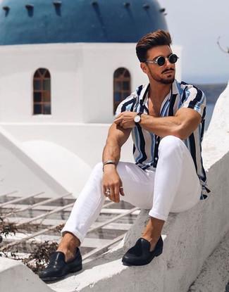 Wie kombinieren: weißes und blaues vertikal gestreiftes Kurzarmhemd, weiße Chinohose, schwarze Leder Slipper, schwarze Sonnenbrille