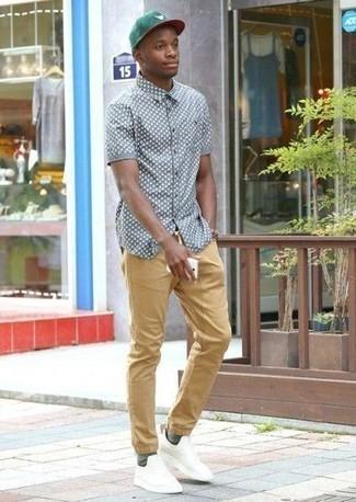Schuhe kombinieren: trends 2020: Vereinigen Sie ein graues bedrucktes Kurzarmhemd mit einer beige Chinohose, um mühelos alles zu meistern, was auch immer der Tag bringen mag. Weiße Sportschuhe leihen Originalität zu einem klassischen Look.