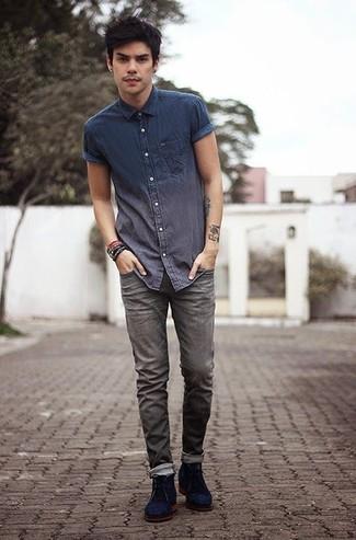 Wie kombinieren: dunkelblaues Chambray Kurzarmhemd, graue Jeans, dunkelblaue Chukka-Stiefel aus Wildleder, dunkelbraunes Armband