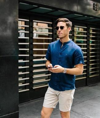 Wie kombinieren: dunkelblaues Kurzarmhemd, hellbeige Shorts, dunkelbraune Sonnenbrille, graue Segeltuchuhr