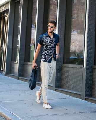 Wie kombinieren: dunkelblaues und weißes Kurzarmhemd mit Blumenmuster, weiße und dunkelblaue vertikal gestreifte Chinohose, weiße Segeltuch niedrige Sneakers, dunkelblaue Shopper Tasche aus Segeltuch