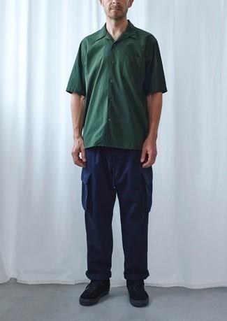 Herren Outfits 2021: Entscheiden Sie sich für ein dunkelgrünes Kurzarmhemd und eine dunkelblaue Cargohose, um einen lockeren, aber dennoch stylischen Look zu erhalten. Schwarze Wildleder niedrige Sneakers fügen sich nahtlos in einer Vielzahl von Outfits ein.