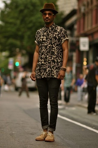 Wie kombinieren: schwarzes Kurzarmhemd mit Blumenmuster, schwarze enge Jeans, beige Chukka-Stiefel aus Wildleder, dunkellila Wollhut