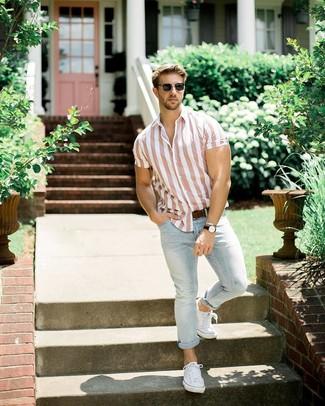 Wie kombinieren: rosa vertikal gestreiftes Kurzarmhemd, hellblaue Jeans, weiße Segeltuch niedrige Sneakers, dunkelbrauner Ledergürtel