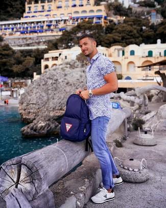 Wie kombinieren: weißes und blaues bedrucktes Kurzarmhemd, blaue Jeans, weiße Sportschuhe, dunkelblauer Segeltuch Rucksack