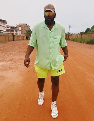 Wie kombinieren: grünes Kurzarmhemd, gelbgrüne Shorts, weiße hohe Sneakers aus Segeltuch, hellbeige Baseballkappe