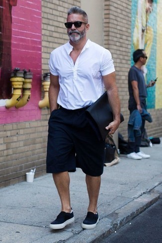 Dunkelblaue Segeltuch Clutch Handtasche kombinieren: trends 2020: Ein weißes Kurzarmhemd und eine dunkelblaue Segeltuch Clutch Handtasche vermitteln eine sorglose und entspannte Atmosphäre. Machen Sie Ihr Outfit mit dunkelblauen Slip-On Sneakers aus Segeltuch eleganter.