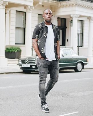 Graue enge Jeans mit Destroyed-Effekten kombinieren – 88 Herren Outfits: Für ein bequemes Couch-Outfit, kombinieren Sie ein schwarzes bedrucktes Kurzarmhemd mit grauen engen Jeans mit Destroyed-Effekten. Schwarze und weiße Segeltuch niedrige Sneakers sind eine einfache Möglichkeit, Ihren Look aufzuwerten.