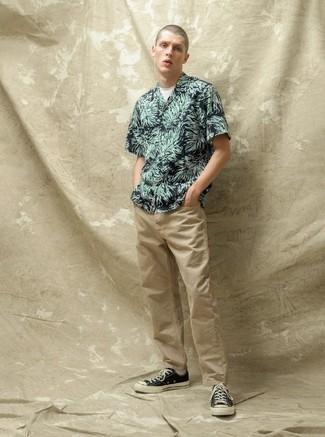 Herren Outfits 2020: Kombinieren Sie ein dunkelgrünes bedrucktes Kurzarmhemd mit beige Jeans für ein großartiges Wochenend-Outfit. Schwarze und weiße Segeltuch niedrige Sneakers fügen sich nahtlos in einer Vielzahl von Outfits ein.