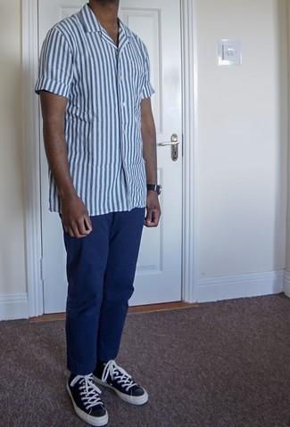 Herren Outfits 2020: Kombinieren Sie ein weißes und blaues vertikal gestreiftes Kurzarmhemd mit einer blauen Chinohose, um mühelos alles zu meistern, was auch immer der Tag bringen mag. Fühlen Sie sich ideenreich? Komplettieren Sie Ihr Outfit mit schwarzen und weißen hohen Sneakers aus Leder.