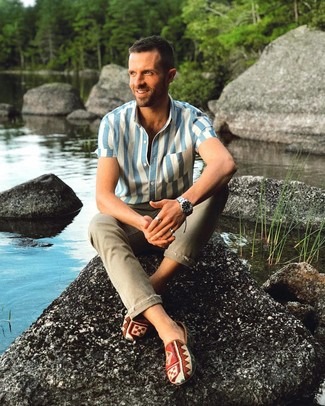 Wie kombinieren: weißes und blaues vertikal gestreiftes Kurzarmhemd, olivgrüne enge Jeans, mehrfarbige bedruckte Slip-On Sneakers aus Segeltuch, silberne Uhr