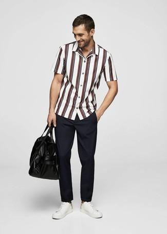 Wie kombinieren: weißes und rotes vertikal gestreiftes Kurzarmhemd, dunkelblaue Chinohose, weiße Leder niedrige Sneakers, schwarze Leder Reisetasche