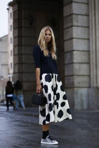 schwarzer Kurzarmpullover, weißer und schwarzer gepunkteter Midirock, graue Segeltuch niedrige Sneakers, schwarze Leder Clutch für Damen