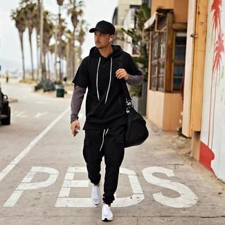 Wie kombinieren: schwarzer Kurzarmpullover mit einem Kapuze, dunkelgraues Langarmshirt, schwarze Jogginghose, weiße Sportschuhe
