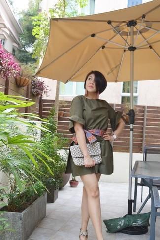 Wie kombinieren: olivgrüner kurzer Jumpsuit, graue Leder Sandaletten mit Schlangenmuster, graue Leder Clutch mit geometrischen Mustern, mehrfarbiger bedruckter Schal