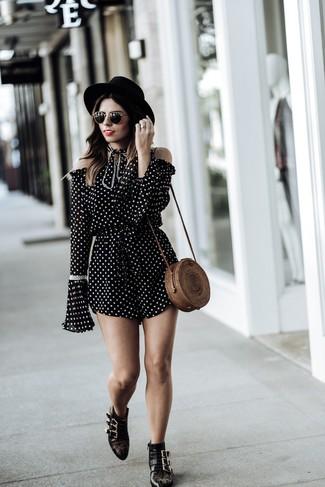 Wie kombinieren: schwarzer und weißer gepunkteter kurzer Jumpsuit, schwarze beschlagene Leder Stiefeletten, braune Stroh Umhängetasche, schwarzer Wollhut