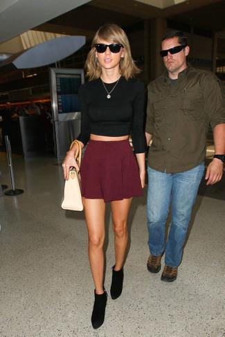 Taylor Swift trägt Schwarzer Kurzer Pullover, Dunkelroter Skaterrock, Schwarze Wildleder Stiefeletten, Hellbeige Shopper Tasche aus Leder