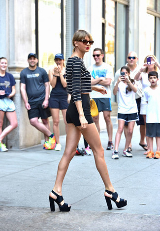 Taylor Swift trägt Dunkelblauer und weißer horizontal gestreifter Kurzer Pullover, Schwarze Shorts, Schwarze klobige Leder Sandaletten, Gelbe Lederhandtasche