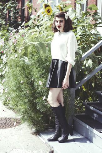 Wie kombinieren: weißer Strick kurzer Pullover, schwarzer Skaterrock aus Leder, schwarze kniehohe Stiefel aus Leder, weiße Fliege
