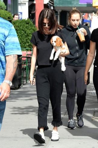 Wie kombinieren: schwarzes kurzes Oberteil, schwarze Fransen Anzughose, weiße Slip-On Sneakers aus Leder, schwarze Sonnenbrille