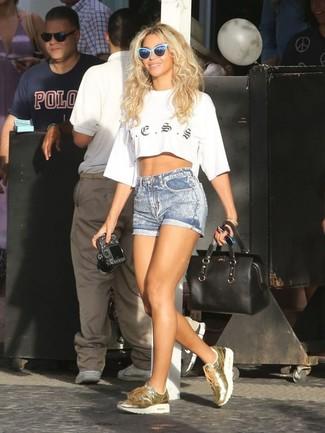 Wie kombinieren: weißes bedrucktes kurzes Oberteil, hellblaue Jeansshorts, goldene Leder niedrige Sneakers, schwarze Leder Reisetasche