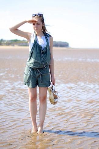 Wie kombinieren: weißes kurzes Oberteil, dunkelgrüne kurze Latzhose, weiße flache Sandalen aus Leder, weiße und schwarze Sonnenbrille
