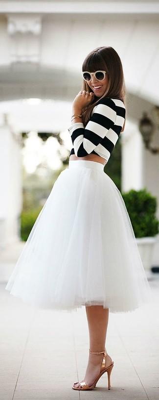 Kombinieren Sie ein weißes und schwarzes horizontal gestreiftes kurzes Oberteil mit einem weißen Midirock aus Tüll, um einen schicken, glamurösen Outfit zu schaffen. Machen Sie Ihr Outfit mit goldenen Leder Sandaletten eleganter.