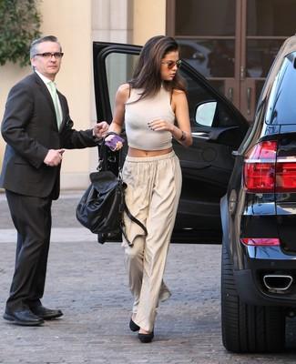 Selena Gomez trägt Weißes Kurzes Oberteil, Hellbeige Weite Hose, Schwarze Wildleder Pumps, Schwarze Satchel-Tasche aus Leder