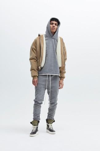 beige Lammfelljacke, grauer Pullover mit einem Kapuze, graue Jogginghose, olivgrüne hohe Sneakers für Herren