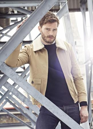 Jamie Dornan trägt Beige Lammfelljacke, Schwarzer Pullover mit Rundhalsausschnitt, Weißes vertikal gestreiftes Langarmhemd, Dunkelblaue Jeans