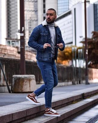 Wie kombinieren: blaue Jeanslammfelljacke, grauer Wollrollkragenpullover, blaue Jeans mit Destroyed-Effekten, rotbraune Wildleder niedrige Sneakers