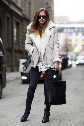 Wie kombinieren: graue Lammfelljacke, weiße und schwarze bedruckte Langarmbluse, schwarze enge Jeans, schwarze Leder Stiefeletten