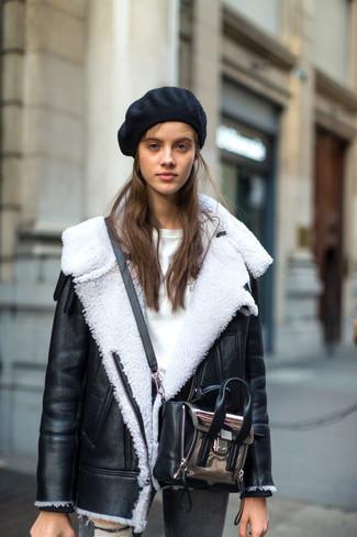schwarze und weiße Lammfelljacke, weißer Pullover mit einem Rundhalsausschnitt, graue enge Jeans mit Destroyed-Effekten, silberne Leder Umhängetasche für Damen
