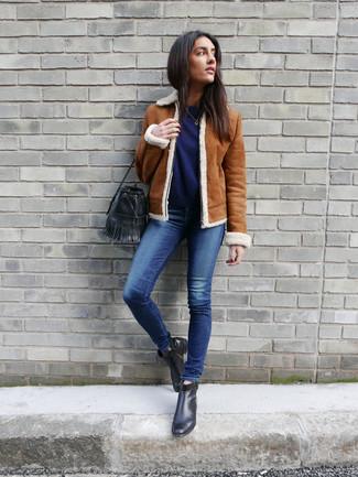 Wie kombinieren: rotbraune Lammfelljacke, dunkelblauer Pullover mit einem Rundhalsausschnitt, blaue enge Jeans, schwarze Leder Stiefeletten