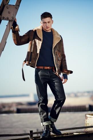 braune Lammfelljacke, dunkelblauer Pullover mit einem Rundhalsausschnitt, schwarze Jeans, schwarze Lederfreizeitstiefel für Herren