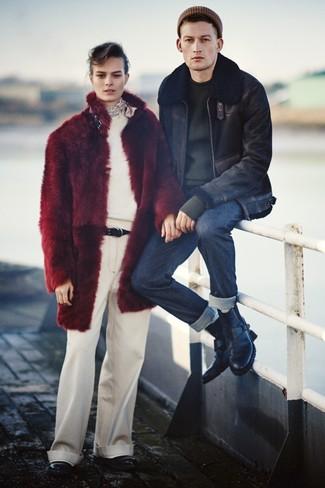 schwarze Lammfelljacke, schwarzer Pullover mit einem Rundhalsausschnitt, dunkelblaue Jeans, schwarze Lederfreizeitstiefel für Herren